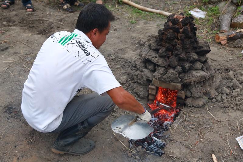 營主幫忙將炭火挖出來