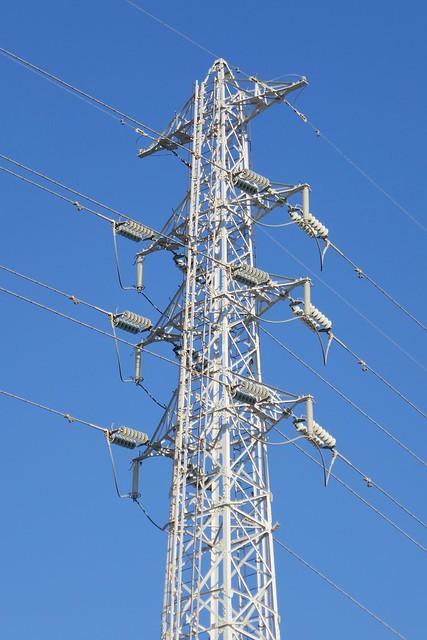 Omiya_Transmission Tower_(2017_12_06)_1_resized_1 高圧送電線の鉄塔の写真。 青空を背景に鉄骨の塔が立つ。 送電線が幾本も伸びている。
