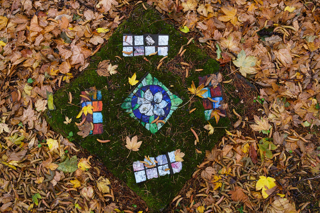 A moss-covered mosaic is surrounded by leaves in the Irvington neighborhood of Portland, Oregon