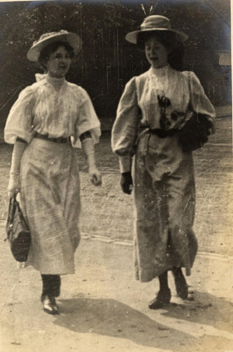 Two women engaged in conversation as they walk, 1908