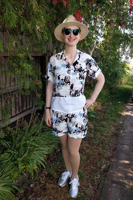 Woman stands against garden fence. She wears matching tropical top and shorts, silver runners and panama hat.