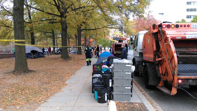 Photo of items stacked neatly on the sidewalk next to two trash trucks parked on the street. Tents can be seen in the distance beyond the police line and city workers walk down the sidewalk.