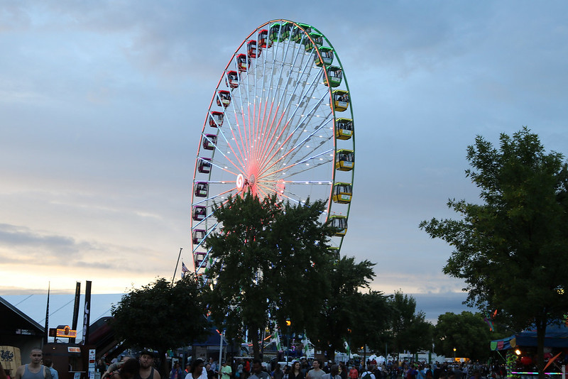 the tall ferris wheel, at an angle at dusk so the colored lights are visible