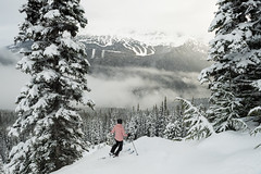 A skier taking in her beautiful surroundings in the mountains