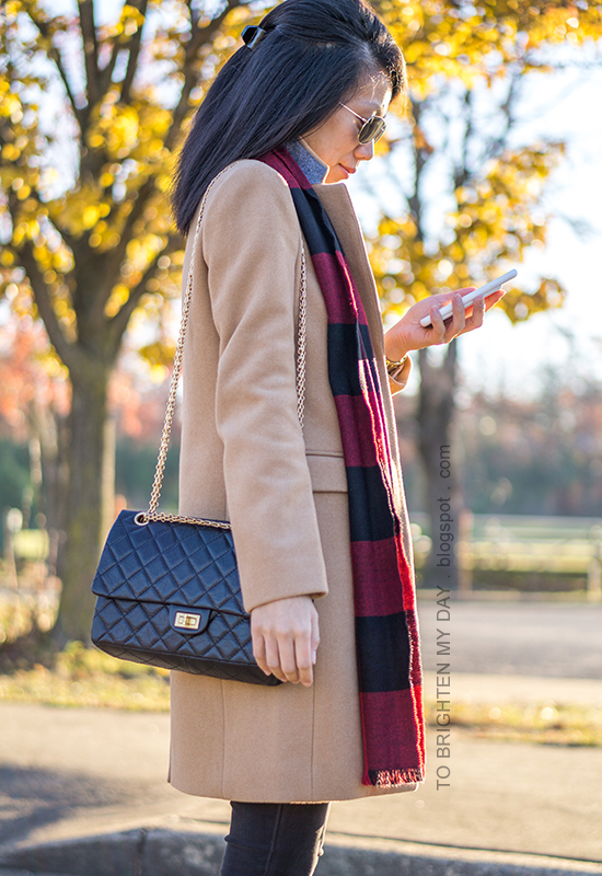 long camel wool coat, red buffalo check scarf, black skinny jeans, black shoulder bag