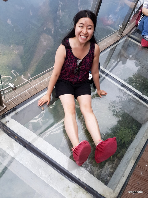 sitting on Tianmen Mountain glass path