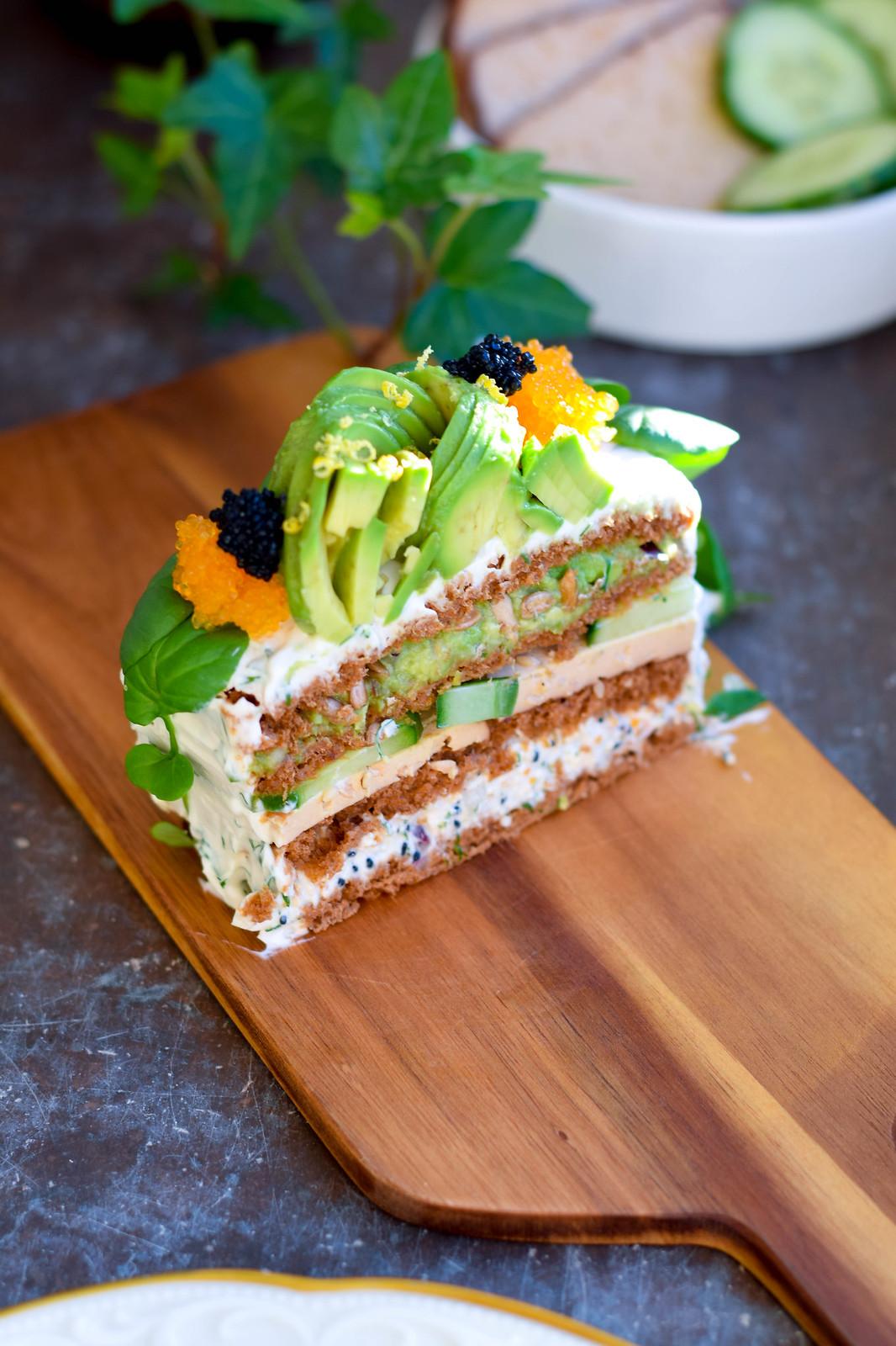En bit uppskuren vegansk smörgåstårta med tre olika fyllningar står på en träskärbräda som är placerad på ett fönsterbläck i mörk marmor