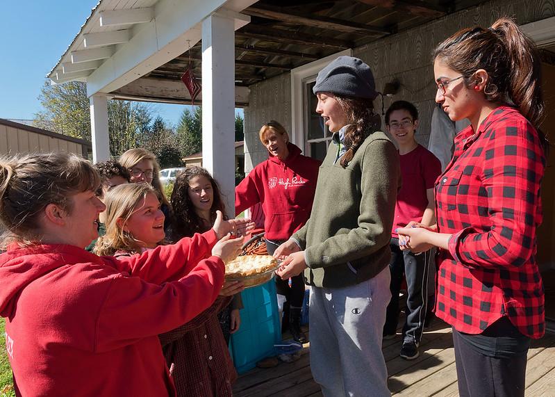 Celebrating Valentina Zavala-Arbelaez's birthday during a lunch break. Becca Richie is handing her the birthday apple pie that Liz Kammeyer baked for the occasion.