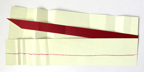 Back of a folded piece of 2-ply paper that was burgundy on one side and cream on the other