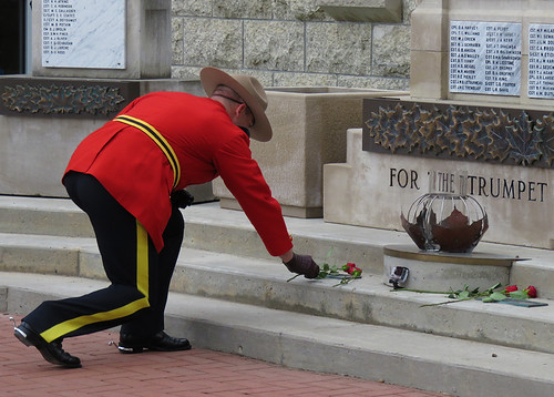 During the ceremony a graduate from the RCMP places a red rose on a cenotaph to remember his fallen comrades