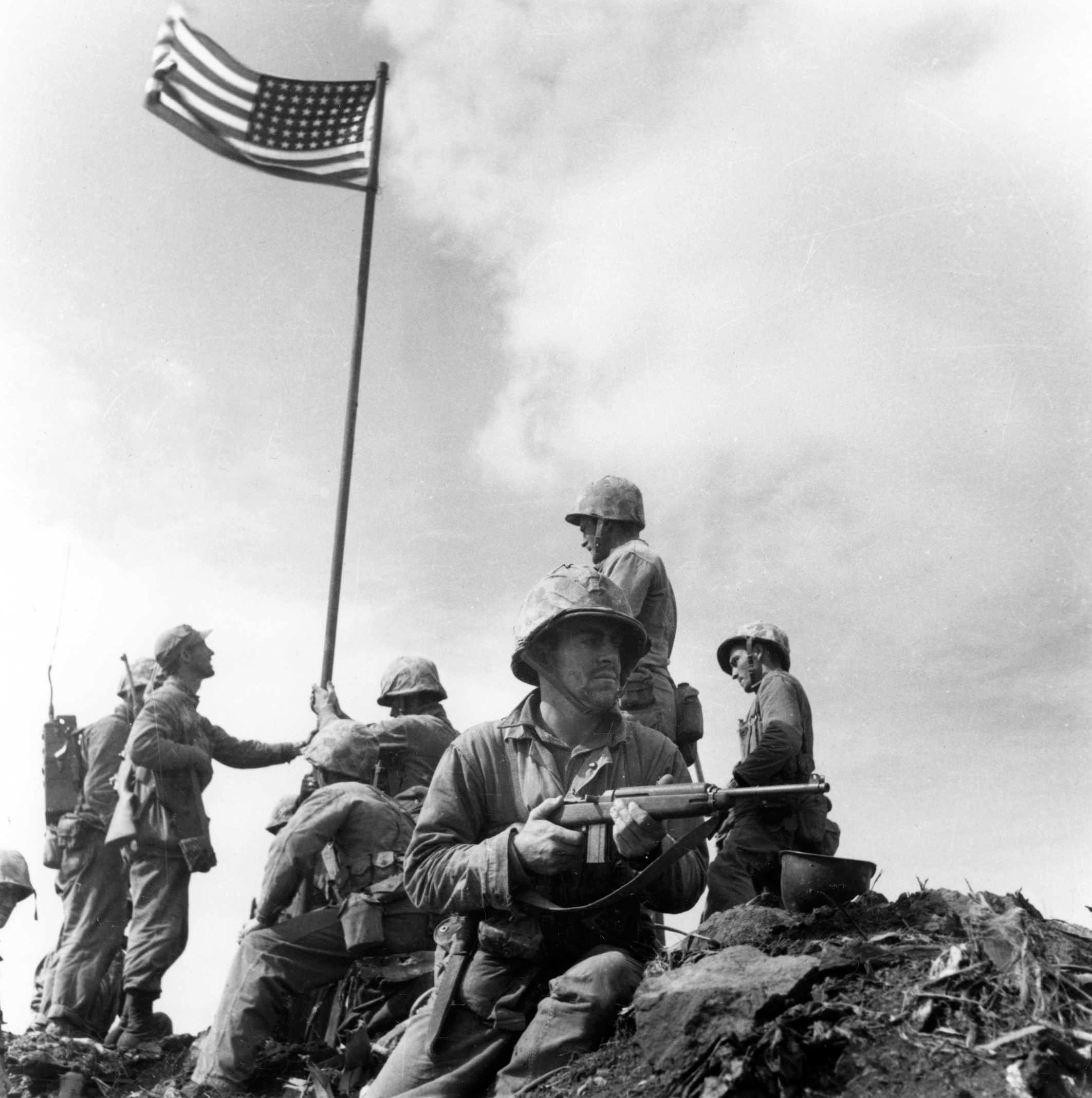 A small flag carried by the 2nd Battalion, 28th Marines is planted atop Mount Suribachi at 10:20 a.m. February 23, 1945. This is the first flag raising on the top of Mt. Suribachi. The famous flag-raising photo was taken when the second flag was put up later that day. This photo was taken by Leatherneck's Lou Lowery. Official U.S. Navy photo.