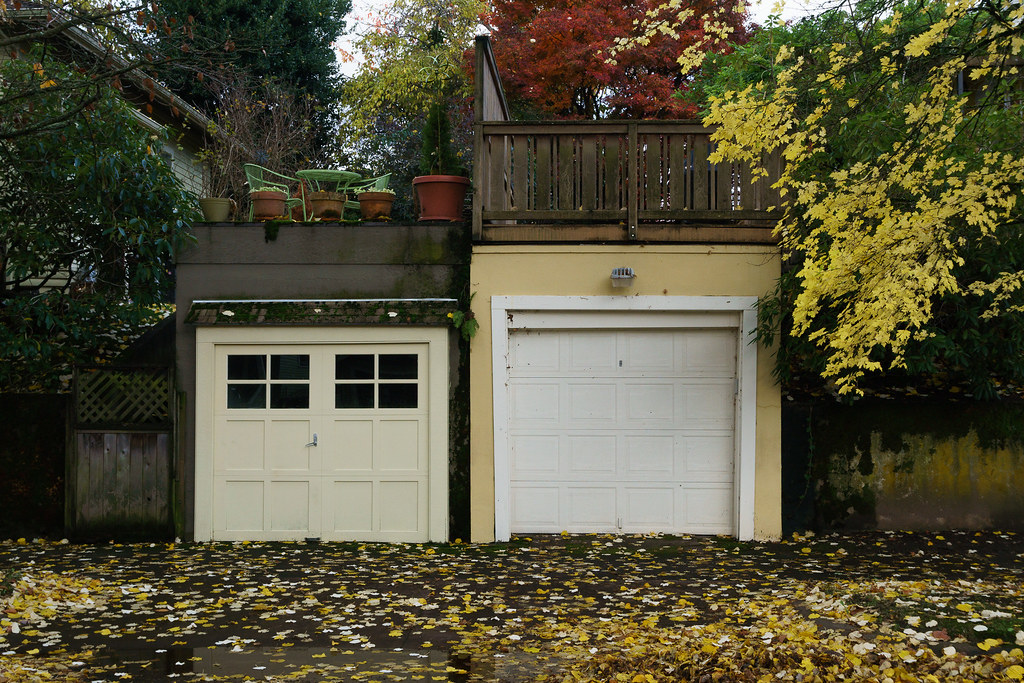 A pair of yellow garages are surrounded by yellow leaves in the Irvington neighborhood of Portland, Oregon