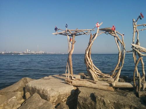 """Toronto"" (3) #toronto #torontodriftwoodsign #driftwood #humberbay #humberbayshorespark #beaches #lakeontario #shorelandarts #skyline #flags #latergram"
