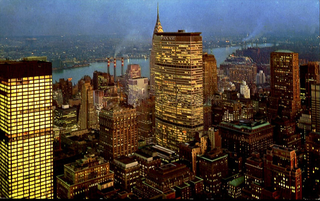 Con Edison smokestacks gently puff away by the East River keeping the lights of Midtown Manhattan glowing on a cold winter evening in December. The Pan Am and Chrysler buildings predominate in the view. New York. 1971