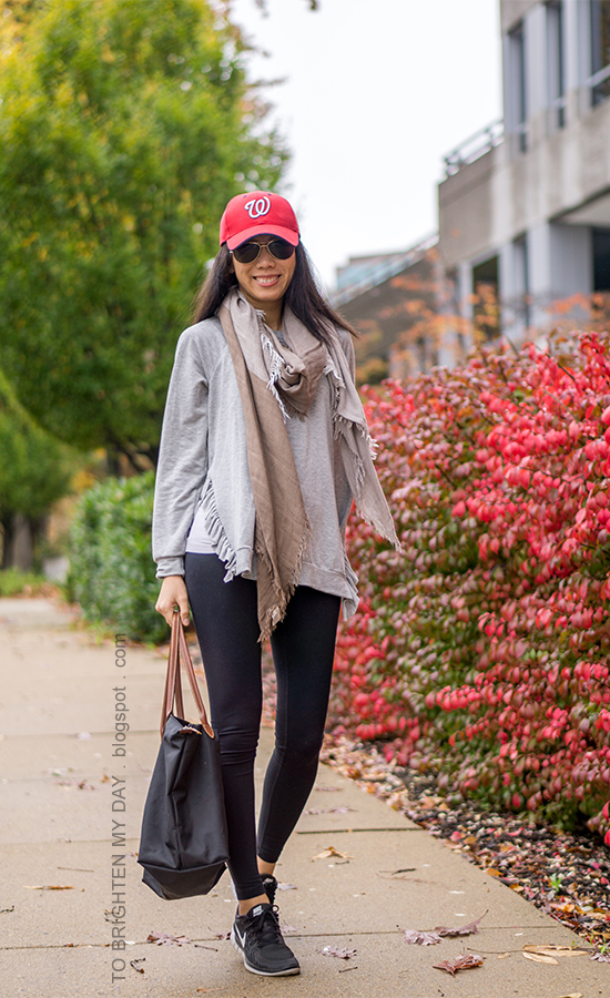 red baseball cap, gray sweatshirt with side ruffles, plaid scarf, black leggings, black tote, black sneakers