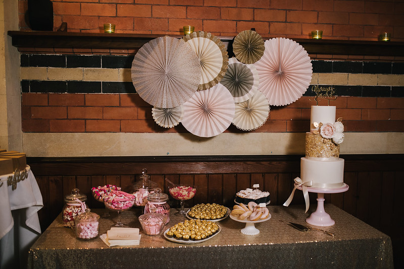 picture of a sweet table at a wedding, glass jars with pink and white sweets