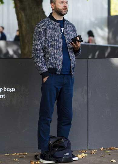 柄ブルゾン×ネイビーTシャツ×ネイビーパンツ×黒スニーカー