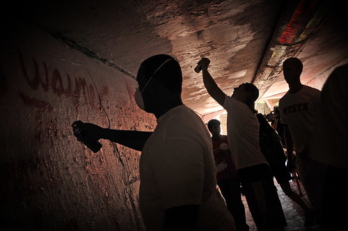 Members of the football team spray paint the Free Expression Tunnel along with other Wolfpack student athletes during a show of Wolfpack Unlimited solidarity.
