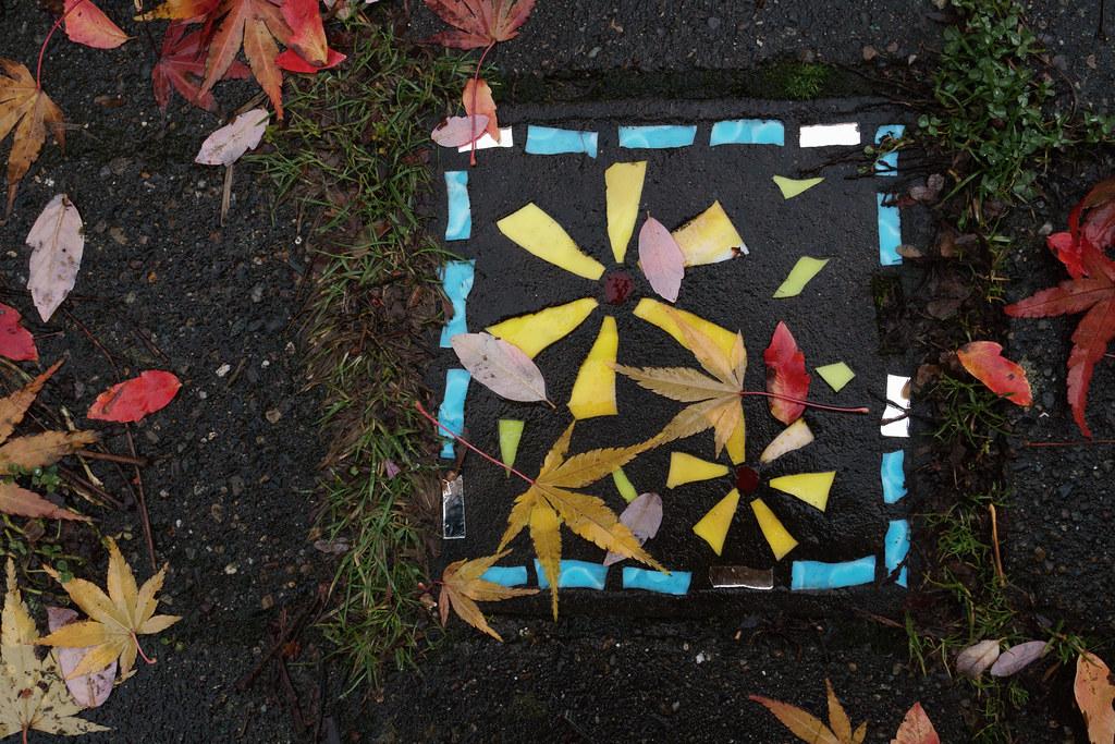 Leaves sit on artwork of flowers in a sidewalk