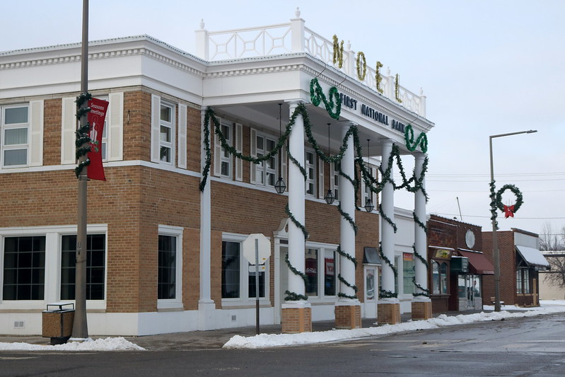 brick building with four white pillars wrapped in greenery, greenery draped across the top front, and gold tinsel letters spelling NOEL at the top
