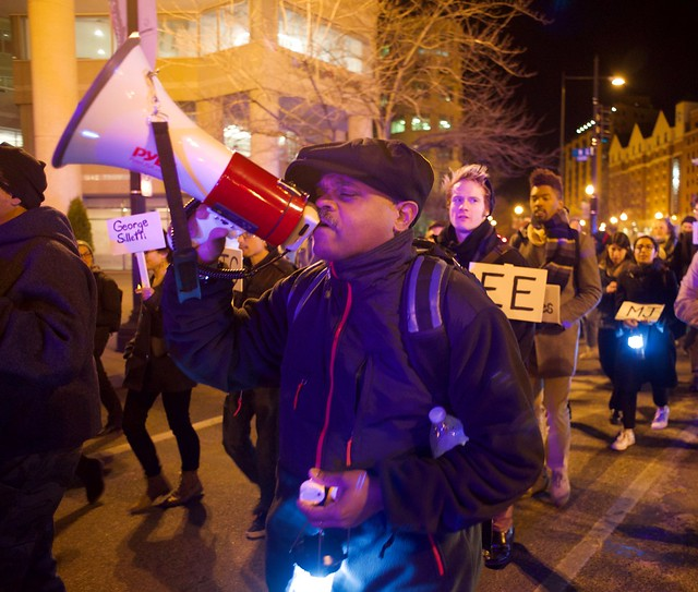 A man amidst a crowd, dressed for cold weather, yelling into a megaphone with his eyes closed.