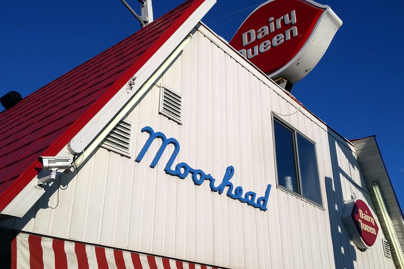 barn-shaped building with a red roof and white sides, with Moorhead written in blue script near the top