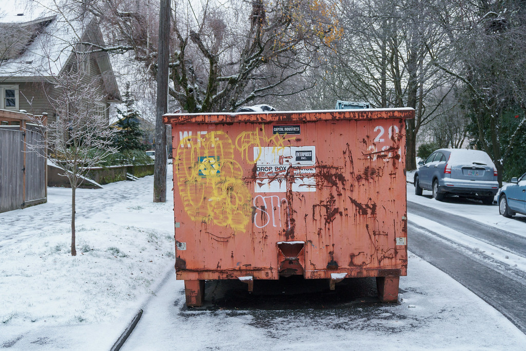 A large orange trash container sits on a snow-covered Siskiyou Street in the Irvington neighborhood of Portland, Oregon