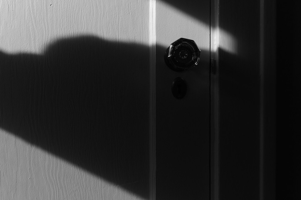 Light breaks through the shadows and almost reaches the doorknob