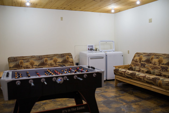 Utility room with foos ball table, washer/dryer and two futons for relaxing