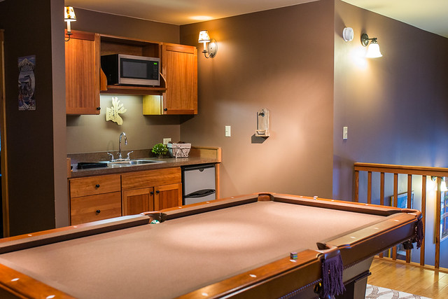 Second floor game room with a pool table and wet bar;