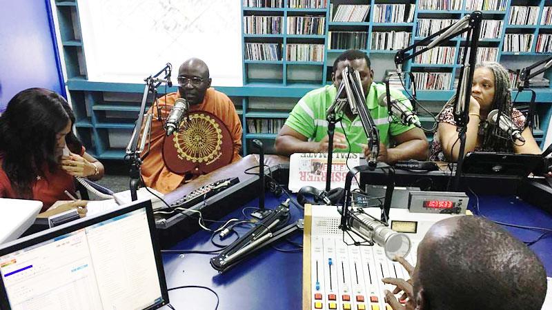 Y.M. Buddharakkhita (kedua dari kiri) seorang bhikkhu asal Uganda, saat memberikan ceramah tentang meditasi kesadaran di stasiun radio di Jamaika