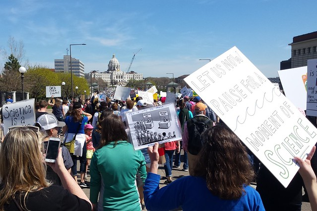 crowd facing the capitol, backs to the camera, one sign visible at right - Let us now pause for a moment of science