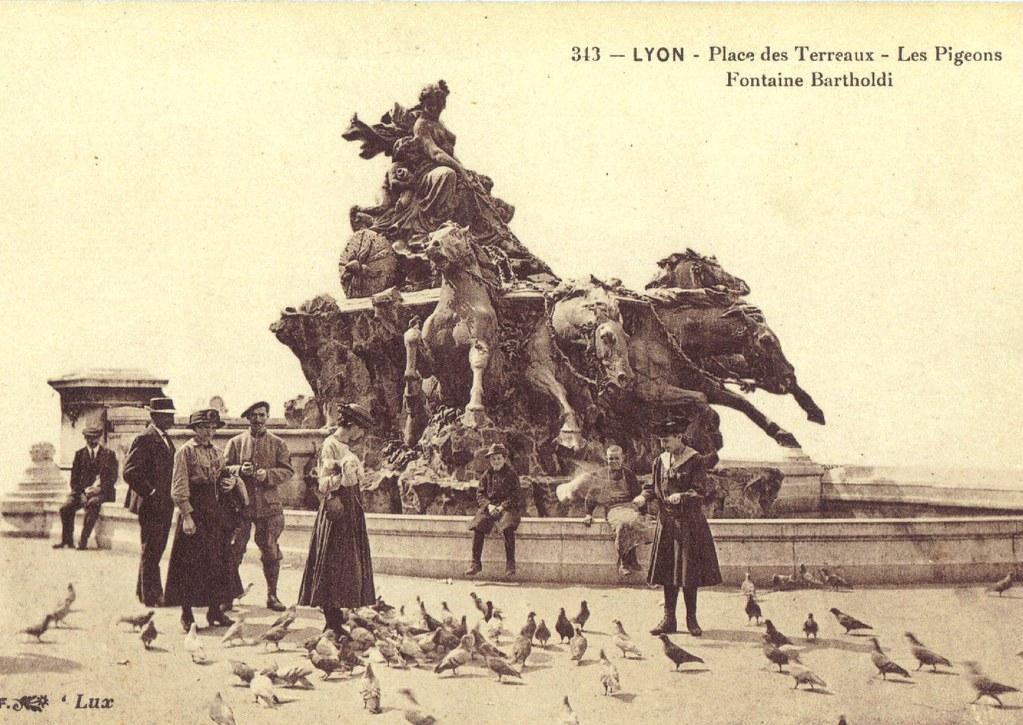 > Fontaine de la place des Terreaux à Lyon avec badauds et pigeons sur une ancienne carte postale.