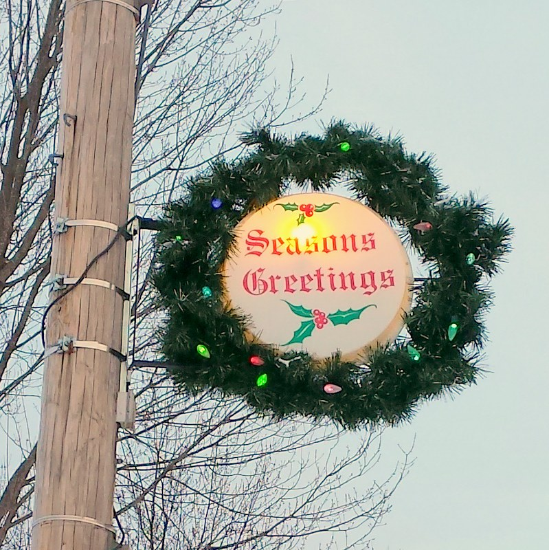 wreath with a white center that says Seasons Greetings