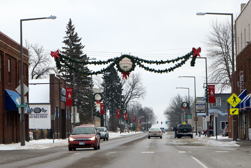 double strand of greenery draped across the street, with big red bows at the corners, and a white circle in a wreath at the center saying Seasons Greetings MILACA