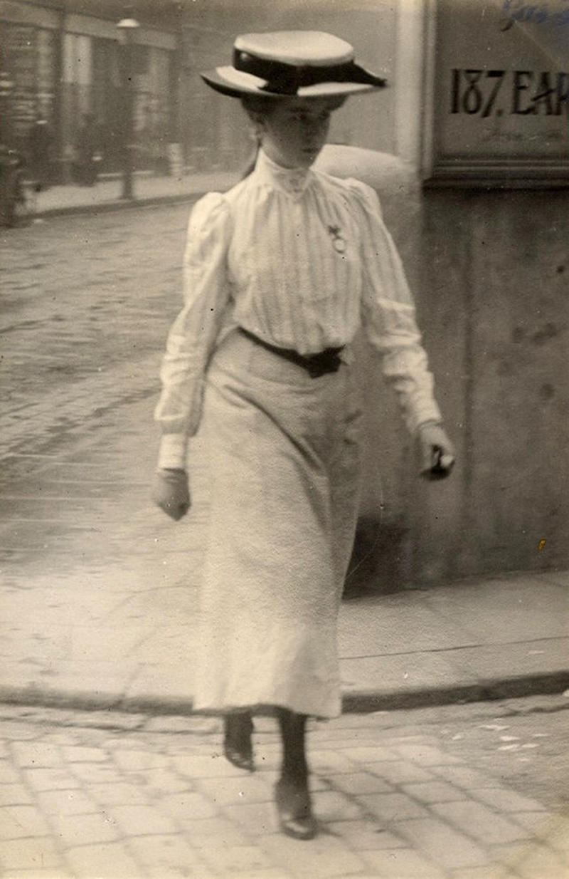 A young woman in Cromwell Road, London on July 12, 1905 in a stylish striped shirt with a belt and an ankle-length skirt