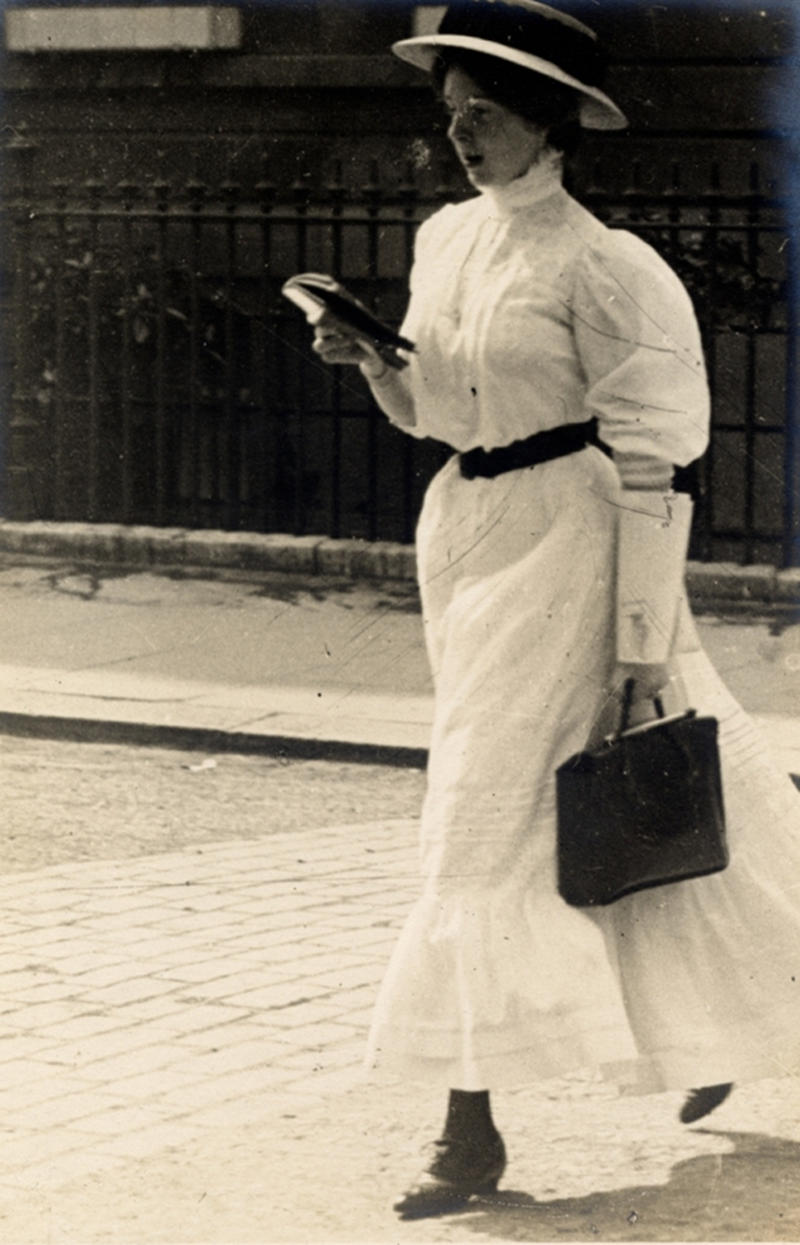 A woman in a formal white dress with black handbag walks along the street in Kensington on June 15, 1908