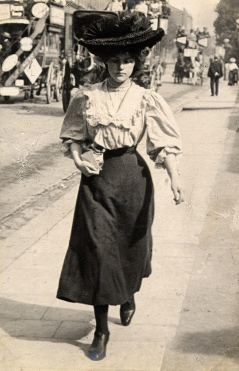 A young woman on Kensington High Street with horse-drawn buses in the background