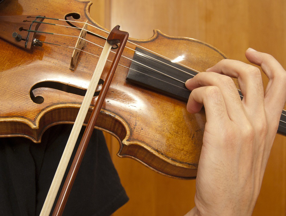 closeup photo of violinist practicing