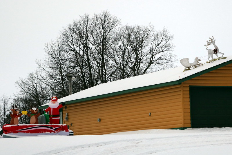 brown garage with a white wire sleigh and reindeer on the roof at the right, a blow-up boat with Santa and standing reindeer at the left