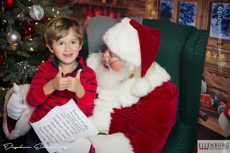 Young boy gives thumbs up to Santa.