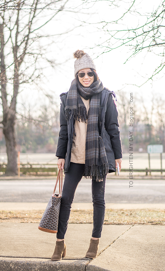 beanie with pom, black parka, green plaid wool scarf, black jeans, patterned tote, camel sweater, suede ankle boots