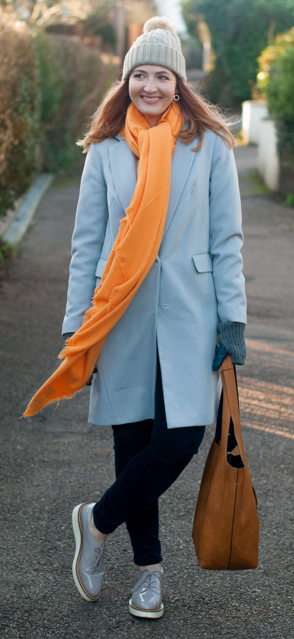 Bold brights winter weather outfit: Tangering orange scarf with pale grey duster coat, blue velvet trousers, grey flatforms and taupe pom pom beanie | Not Dressed As Lamb, over 40 style