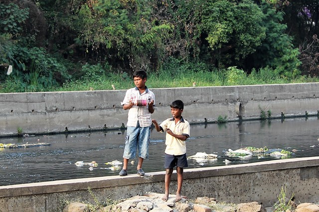 Children enjoy flying kites, oblivious to the state of the poisoned and garbage-laden river flowing behind them.