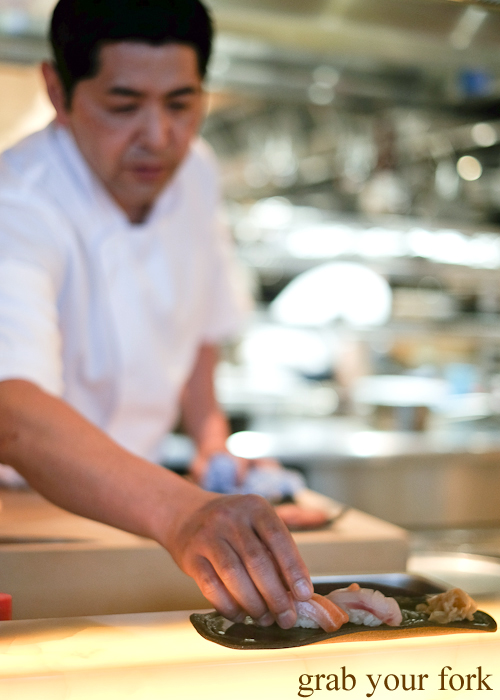 Chef Ryuichi Yoshii presenting salmon and bar cod sushi at Fujisaki by Lotus at Barangaroo in Sydney