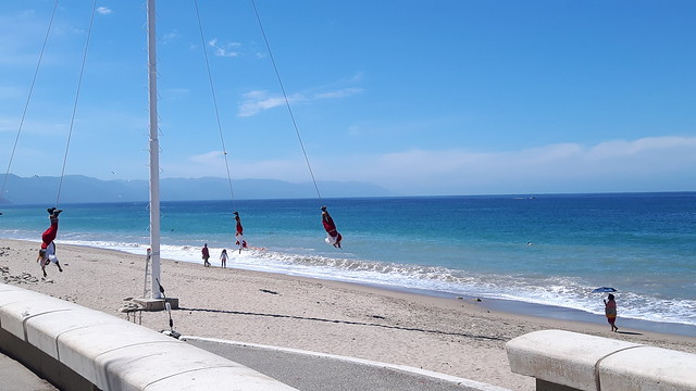 Voladores on the beach - men hanging upside down from ropes swinging around a pole