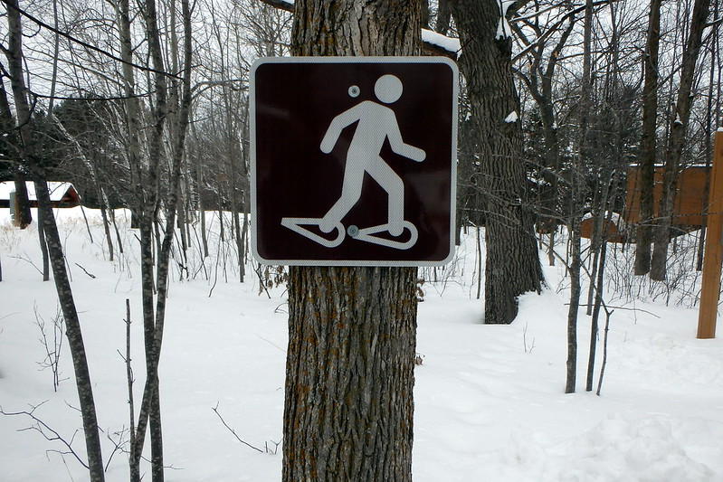 Brown metal sign with a stick figure wearing snowshoes.