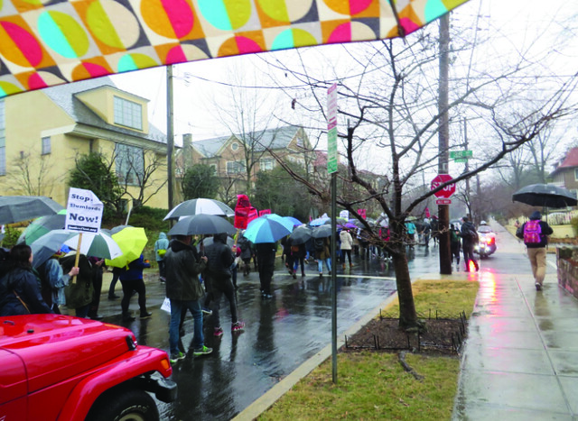 A street filled with pedestrians holding signs and umbrellas.