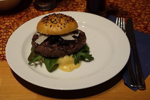 Burger mit selbstgebackenem Sesam-Bun, frisch angerührter Walnussöl-Honig-Senf-Mayonnaise, etwas Salat, köstlichen Balsamico-Zwiebeln, Parmesan und Patty aus Pferdefilet (mein erster)