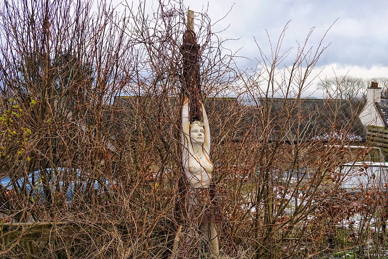 A female statue rising from the undergrowth